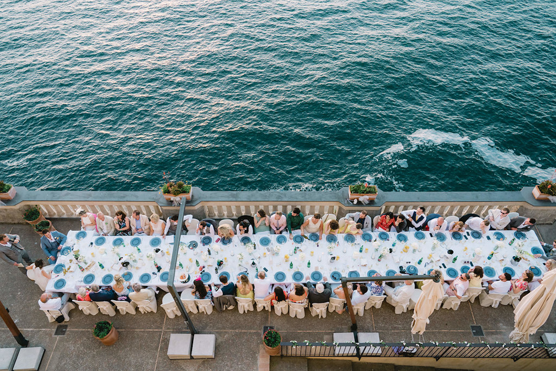 table with people eating dinner on a terrace overlooking the sea